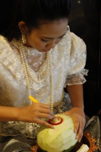 A female participates in fruit carving during the International Association of Universities